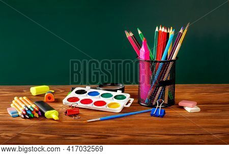 Back To School! School Supplies, On A Wooden Table Against The Background Of A Chalkboard.
