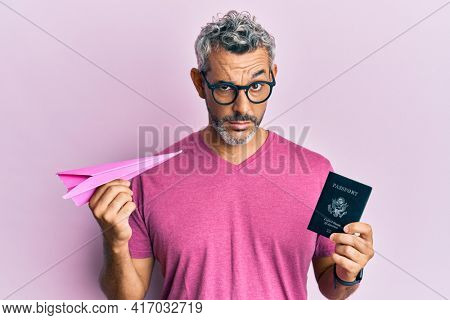 Middle age grey-haired man holding paper plane and passport skeptic and nervous, frowning upset because of problem. negative person.