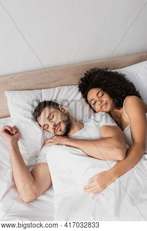 High Angle View Of Multiethnic Couple Sleeping In Bed.