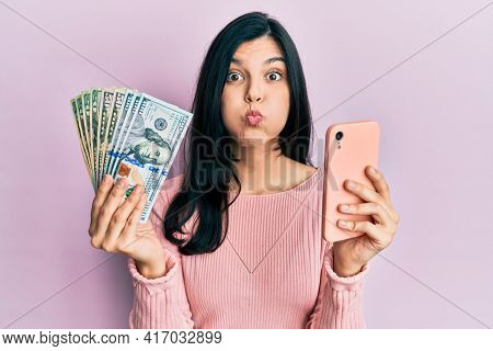 Young hispanic woman using smartphone holding united states dollar banknotes puffing cheeks with funny face. mouth inflated with air, catching air.