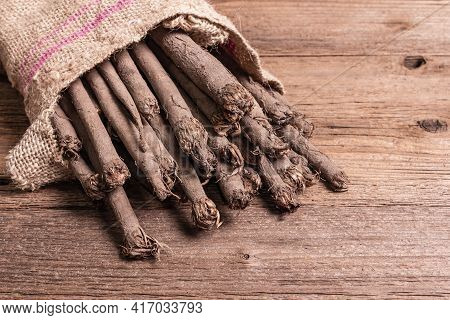 Raw Scorzonera Or Spanish Salsify In A Sackcloth Bag On Vintage Wooden Table