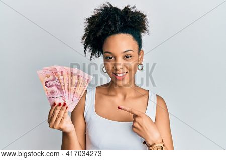 Young african american girl holding thai baht banknotes smiling happy pointing with hand and finger