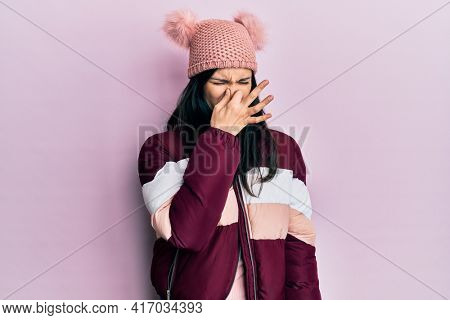 Young hispanic woman wearing wool winter sweater and cap smelling something stinky and disgusting, intolerable smell, holding breath with fingers on nose. bad smell