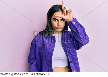 Young brunette woman wearing casual clothes making fun of people with fingers on forehead doing loser gesture mocking and insulting.