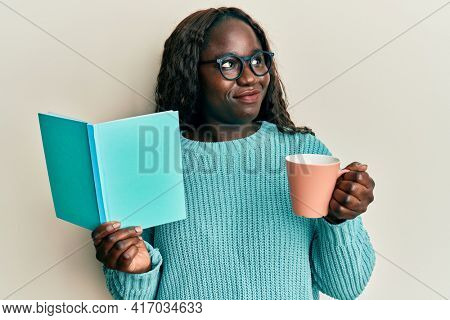 African young woman reading a book and drinking a cup of coffee smiling looking to the side and staring away thinking.