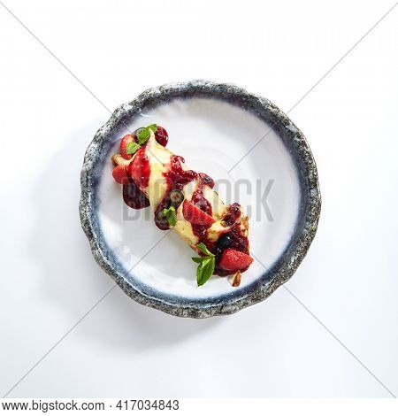 French Style Crepes - Cream Crepes with Berry and Fruit. Pancake Breakfast on white and blue plate isolated on white background. Mixed berry crepes garnished with mint and sweet sauce top view