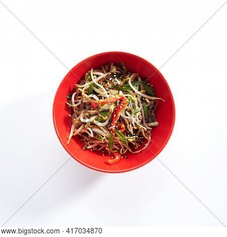 Udon noodle with teriyaki chicken and vegetable. Asian style noodle food on white background. Teriyaki chicken noodle in red bowl with sesame and onion. Top view