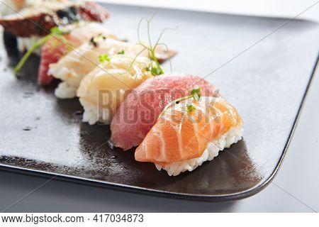 Japanese Nigiri Sushi Set - Sushi with Rice and Various Seafood. Salmon, Tuna, Sea Scallop and other seafood fish. Nigiri Sushi row on black slate platter. Isolated on white background