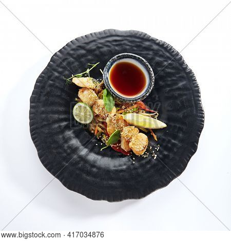 Teppanyaki Style Scallop - Grilled Sea Scallop with Soy Sauce and Vegetables. Japanese Teppanyaki Scallop garnished with lemon and fresh basil leaf. Black asian plate on white background Top view