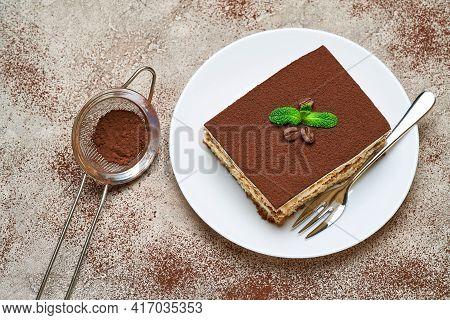 Portion Of Traditional Italian Tiramisu Dessert On Grey Concrete Background