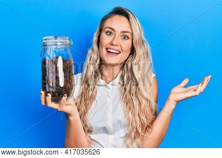 Beautiful young blonde woman holding raisins bowl celebrating achievement with happy smile and winner expression with raised hand