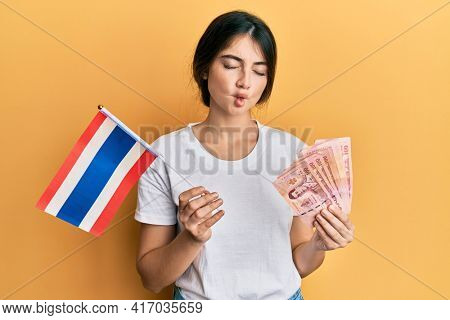 Young caucasian woman holding thailand flag and baht banknotes making fish face with mouth and squinting eyes, crazy and comical.