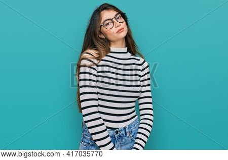 Young beautiful teen girl wearing casual clothes and glasses relaxed with serious expression on face. simple and natural looking at the camera.