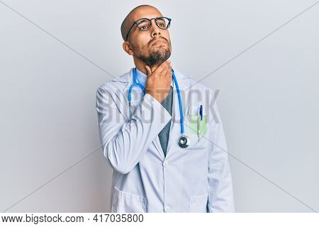 Hispanic adult man wearing doctor uniform and stethoscope touching painful neck, sore throat for flu, clod and infection