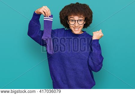 Young hispanic girl holding sporty sock screaming proud, celebrating victory and success very excited with raised arms