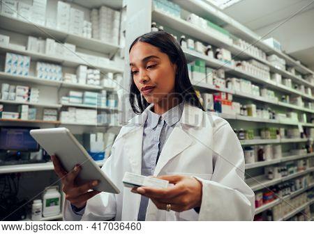 Woman In Chemist Wearing Labcoat Checking Medicine Details In Digital Tablet