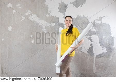 A Woman In A Bright Yellow T-shirt Holds 2 Rolls Of Wallpaper Against The Old Wall. Repair Work, Wal