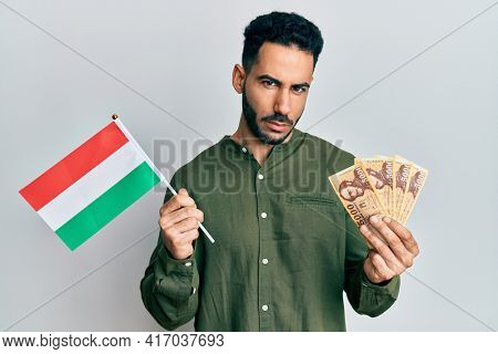 Young hispanic man holding hungary flag and forints skeptic and nervous, frowning upset because of problem. negative person.