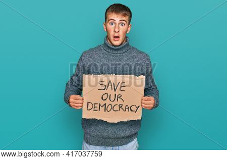 Young blond man holding save our democracy protest banner scared and amazed with open mouth for surprise, disbelief face