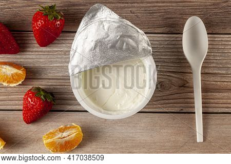 Flat Lay Image Of A Store Bought Plastic Cup Of Plain Low Fat Greek Yogurt With The Aluminum Foil Se