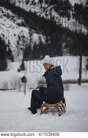 Teenager With A Smile On His Face Sits On A Wooden Historic Sledge And After A Ride Looks Back At Th