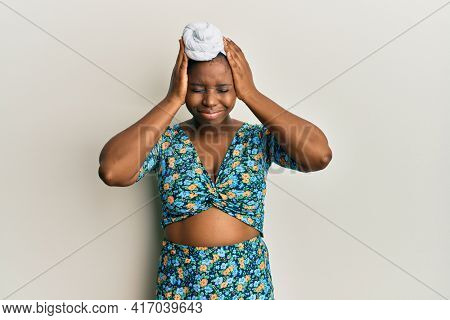 Young african woman wearing hair turban and african style suffering from headache desperate and stressed because pain and migraine. hands on head.