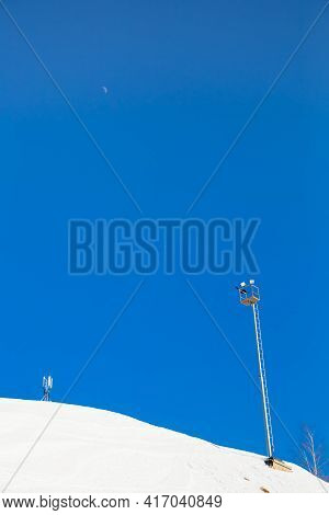 Ski Resort, Gentle Snow Slope With Artificial Lighting Towers. Mountain Slope For Skiing And Snowboa