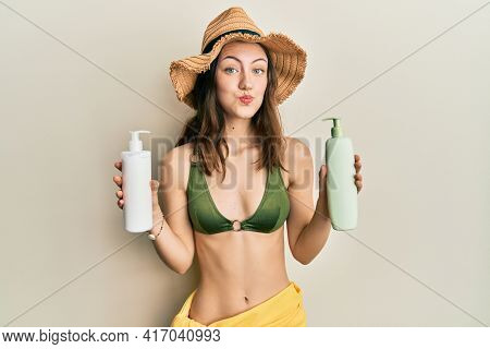 Young brunette woman wearing bikini holding sunscreen lotions puffing cheeks with funny face. mouth inflated with air, catching air.