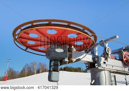 Large Spinning Wheel With Electric Cable Hoist Motor In A Ski Resort. The Drive Mechanism Against Th