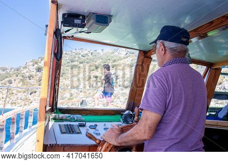 Boat Captain Controls Ship. Yacht Steering Wheel And Control Panel. Ready To Sea Travel. Wooden Deck