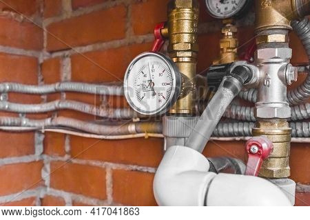 Pressure Gauge On A Pipe System With Thermal Insulation Against The Background Of A Heating Unit At