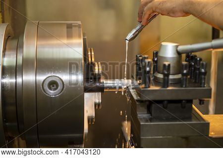 The Hand Of Machine Operator Setting The Coolant Tube On Late Machine. The Operation Of Lathe Machin