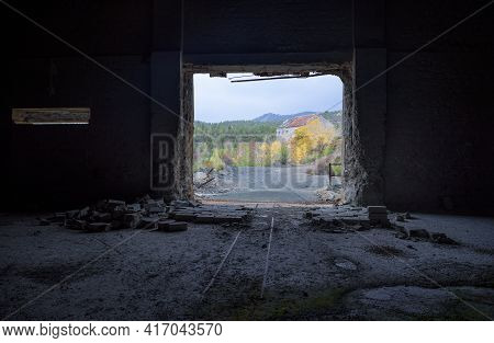 View Through The Door Of Abandoned Factory With Rails And Broken Brick Wall Inside And Autumn Landsc