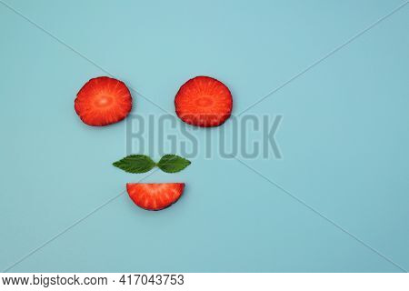 Circles And Semicircles Of Red Ripe Strawberries And Green Mint Leaves On A Blue Background. Mister