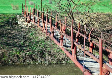 Suspension Old Footbridge Over The River . Old Bridge Constructed With Metal Balustrade And Wooden P