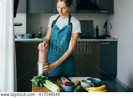 A Charming Housewife In An Apron Prepares A Spring Berry Smoothie In A Blender. Young Wellness Woman