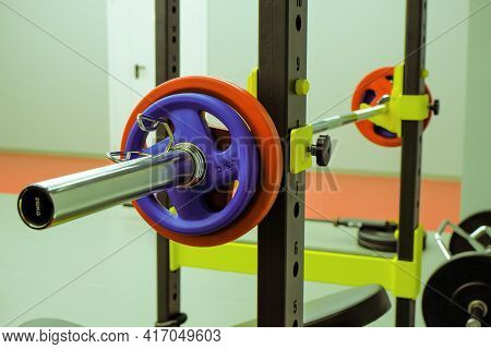 A Barbell With Weights For Fitness Lies In The Gym On An Adjustable Rack,