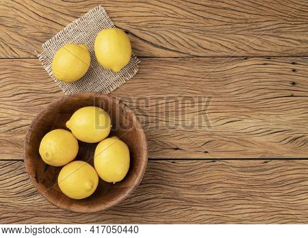 Sicilian Lemons In A Bowl Over Wooden Table With Copy Space.