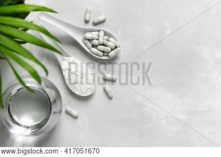 Collagen Powder, Tablets And A Glass Of Water On A Gray Background With A Copy Space. Extra Protein