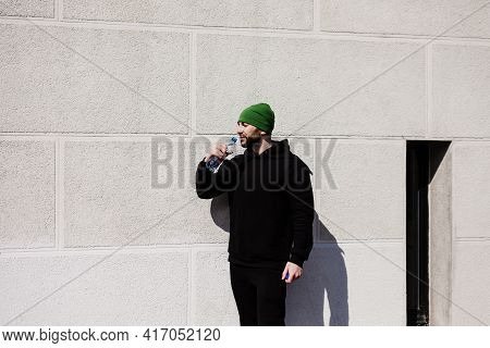 Thirsty Caucasian Male Jogger In Active Wear And Holding Water Bottle Get Refreshment After Jogging,