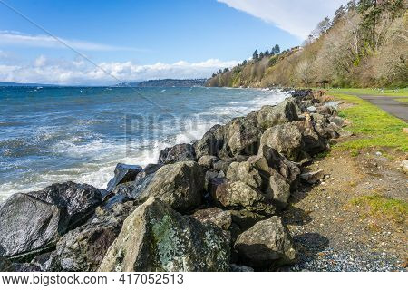 Rocks Line The Shore At Saltwater State Park In Des Moines, Washington. It Is A Windy Day.