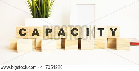 Wooden Cubes With Letters On A White Table. The Word Is Capacity. White Background.