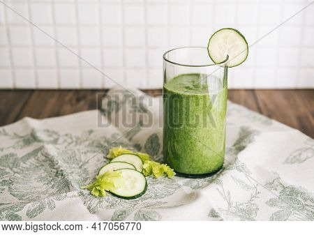 Green Smoothie With Celery And Cucumber In Crystal Glass On A Gray Cloth Of Green Leaves On A Dark W