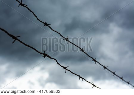Two Rows Of Barbed Wire Backlit With Dark Storm Clouds In The Background. Selective Focus. Immigrati