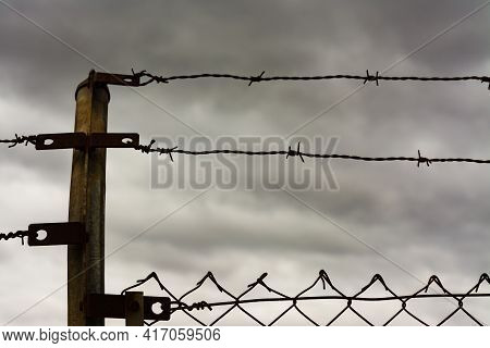 Two Rows Of Barbed Wire On Top Of A Fence With Storm Clouds In The Background. Immigration, Escape O