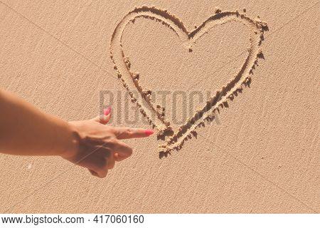 Female Hand Draws A Heart Sign On A Coastal Sand, Beach Love Mark