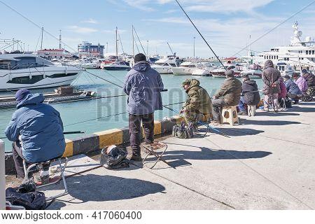 Sochi, Russia - February 26, 2020: In Winter, Fishermen Fish In The Seaport Of Sochi.