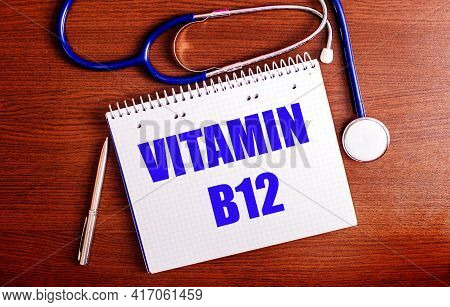 On A Wooden Table Are A Pen, A Stethoscope, And A Notebook Labeled Vitamin B12. Medical Concept