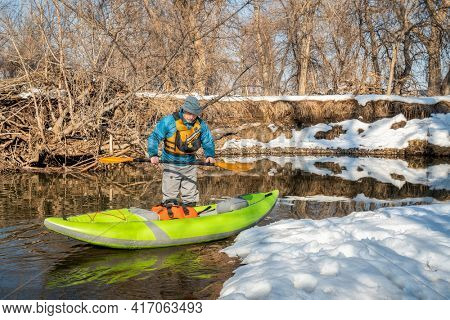 senior male paddler is launching an inflatable whitewater kayak on a small river - Poudre River in Fort Collins, Colorado, winter or early spring scenery