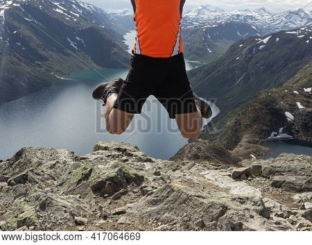 Besseggen, Norway- August,2018. View Of A Young Man In A High Jump With Legs Tucked In Against The B